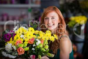 Happy female florist holding bunch of flowers