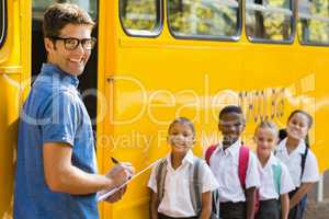 Smiling teacher updating check list of kids while entering in bu