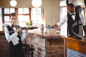 Female bartender holding a serving tray with two cocktail glass