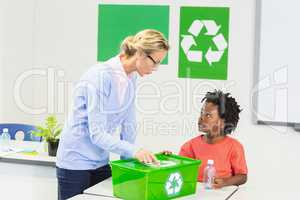 Teacher and schoolboy discussing about recycle logo