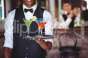Bartender holding serving tray with cocktail glasses