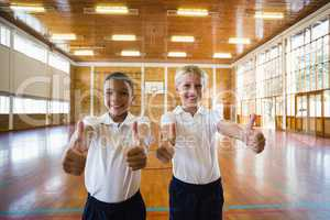 Smiling boys showing thumbs up in school gym