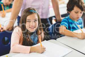 School girl doing homework in classroom