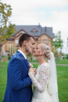 The groom kisses the bride tenderly