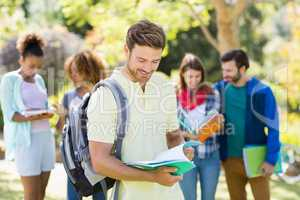 College boy reading notes with friends in background