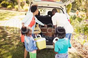 Happy family taking objects out of the car