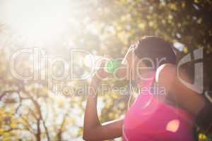 Low angle view of sporty woman drinking water
