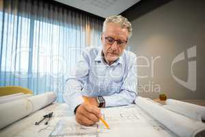 Architect working on blueprint at desk