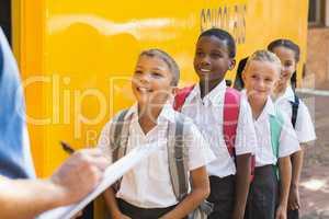 Teacher updating check list of kids