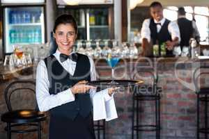 Portrait of bartender holding serving tray with glass of cocktai