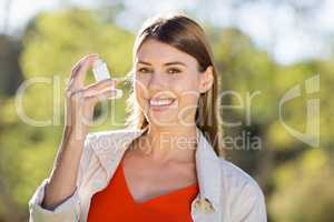 Portrait of beautiful woman using asthma inhaler