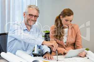 Businesswoman using digital tablet while coworker working on blu