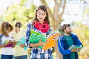 College girl reading notes with friends in background