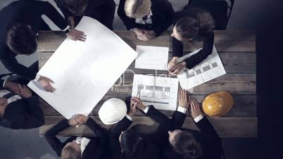 Business people looking at building blueprint