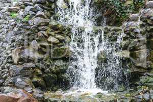 Kleiner Wasserfall, Kaskaden fließt über moosige Felsesteine