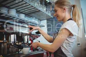 Side view of waitress using coffee maker at cafe