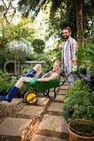 Portrait of cheerful colleagues enjoying with wheelbarrow at gar