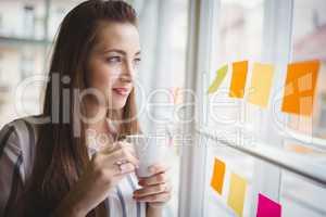 Businesswoman looking through window while having coffee in crea