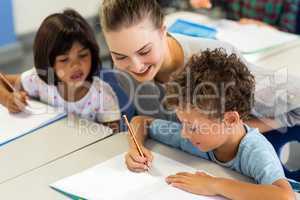 teacher helping schoolchildren to write on book