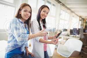 Female colleagues with digital tablet and mobile phone in office