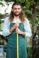 Portrait of happy gardener holding work tool at garden