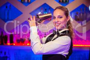 Barmaid with cocktail shaker at counter