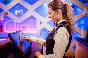 Barmaid using modern cash register at bar counter