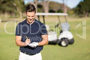 Smiling golfer writing on score card