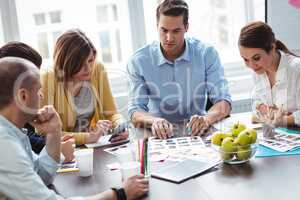 Editors with documents working in meeting room
