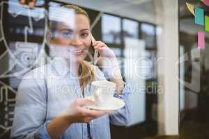 Portrait of businesswoman talking on phone during coffee break