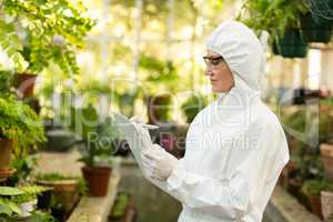 Female scientist wearing clean suit writing in clipboard