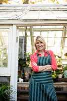 Confident woman standing at doorway in greenhouse