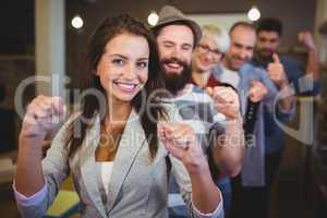 Coworkers cheering with clenched fist in creative office