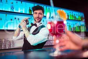 Handsome barkeeper preparing cocktail at bar counter