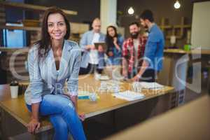 Smart businesswoman sitting on table in office