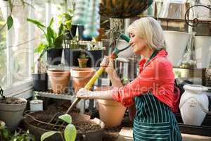 Female gardener digging soil with gardening fork
