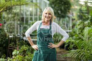 Mature woman standing with hand on hip at greenhouse