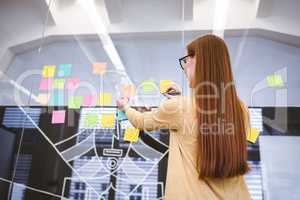 Businesswoman writing on multi colored sticky notes on glass