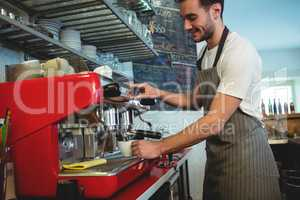 Happy barista using coffee maker at cafe