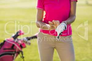 Midsection of woman wearing golf glove
