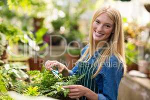 Portrait of female gardener smiling while pruning