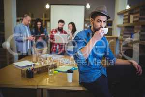 Stylish businessman drinking coffee while sitting at table