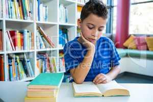 Elementary boy reading book in school library