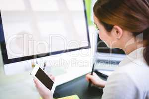 Graphic designer holding phone while working at desk
