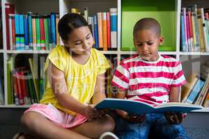 Elementary students reading book at library in school