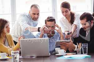 Irritated businessman in between coworkers showing technologies