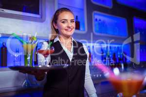 Portrait of beautiful bartender holding serving tray