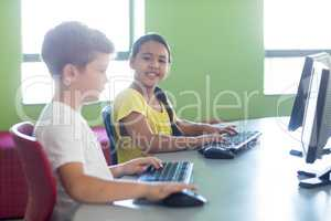 Cute girl with male classmate using computer