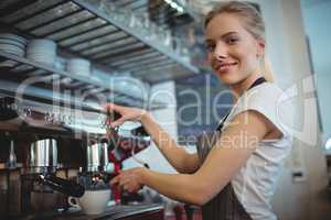 Portrait of waitress using coffee maker at cafeteria
