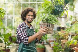 Happy male gardener holding potted plant in wicker basket